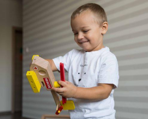 Chlapec sa hra s drevenou stavebnicou vrtulnika